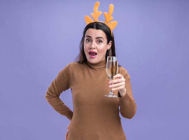 Giovane bella ragazza sorpresa che porta maglione marrone con il cerchio di capelli di natale che tiene vetro di champagne isolato su priorità bassa blu