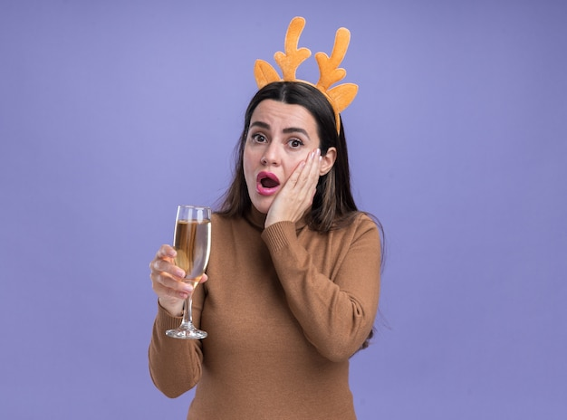 Giovane bella ragazza sorpresa che porta maglione marrone con il cerchio di capelli di natale che tiene vetro di champagne che mette la mano sulla guancia isolata su fondo blu