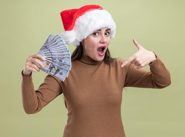 Удивленная молодая красивая девушка в рождественской шапке держит и указывает на деньги, изолированные на оливково-зеленой стене
