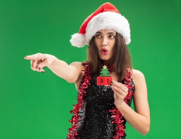 Surprised young beautiful girl wearing christmas hat with garland on neck holding christmas toy points at side isolated on green wall
