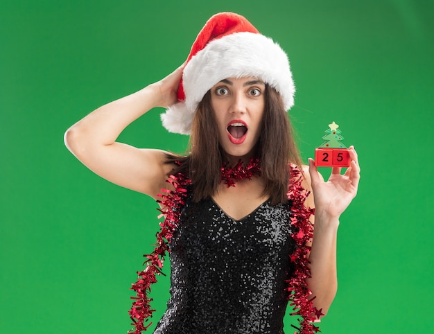 Surprised young beautiful girl wearing christmas hat with garland on neck holding christmas toy putting hand on head isolated on green wall