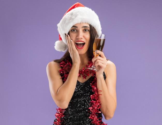 Giovane bella ragazza sorpresa che porta il cappello di natale con la ghirlanda sul collo che tiene un bicchiere di champagne mettendo la mano sulla guancia isolata su sfondo viola