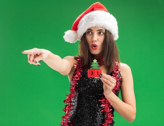緑の壁に隔離された側にクリスマスのおもちゃのポイントを保持している首に花輪とクリスマスの帽子をかぶって驚いた若い美しい少女