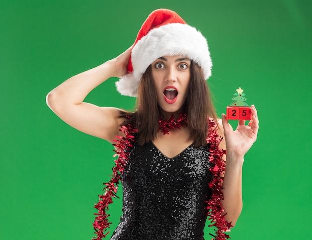 緑の壁で隔離の頭に手を置くクリスマスのおもちゃを保持している首に花輪とクリスマスの帽子をかぶって驚いた若い美しい少女