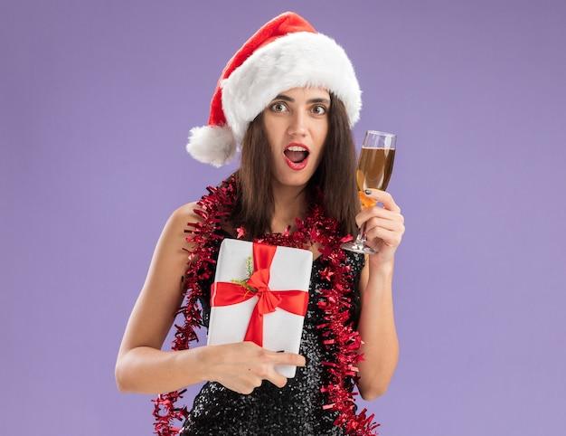 보라색 배경에 고립 된 샴페인 잔 선물 상자를 들고 목에 갈 랜드와 함께 크리스마스 모자를 쓰고 놀란 된 젊은 아름 다운 소녀