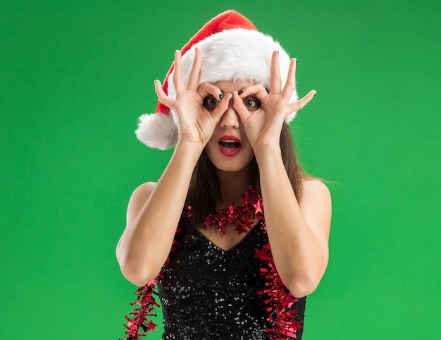 緑の壁に分離された外観のジェスチャーを示す首に花輪とクリスマスの帽子をかぶって驚いた若い美しい少女