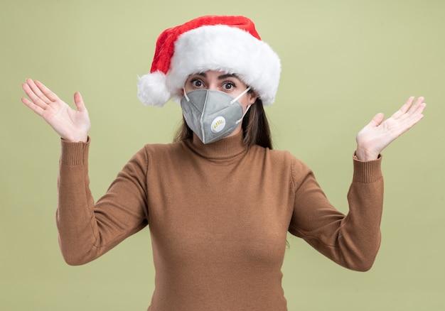 オリーブグリーンの背景に分離された手を広げて医療マスクとクリスマス帽子をかぶって驚いた若い美しい少女