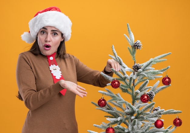 オレンジ色の壁に隔離されたクリスマス ツリーの近くに立っているネクタイでクリスマス帽子をかぶっている美しい少女を驚かせた