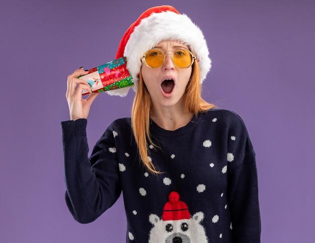 Giovane bella ragazza sorpresa che indossa maglione e cappello di natale con i vetri che tengono la tazza di natale sull'orecchio isolato su fondo viola