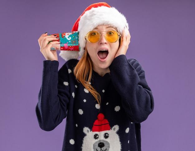 Giovane bella ragazza sorpresa che indossa maglione e cappello di natale con i vetri che tengono la tazza di natale sull'orecchio che mette la mano sulla guancia isolata su fondo viola