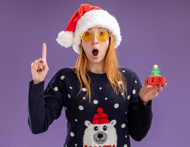 Surprised young beautiful girl wearing christmas sweater and hat with glasses holding christmas toy points at up isolated on purple wall