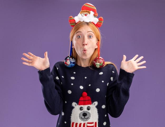 La giovane bella ragazza sorpresa che porta il maglione di natale con il cerchio dei capelli di natale ha appeso le palle di natale sull'orecchio diffondendo le mani isolate su fondo viola