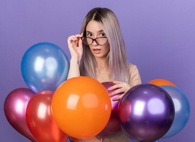 青い壁に隔離された風船の後ろに立っている眼鏡をかけて驚いた若い美しい少女