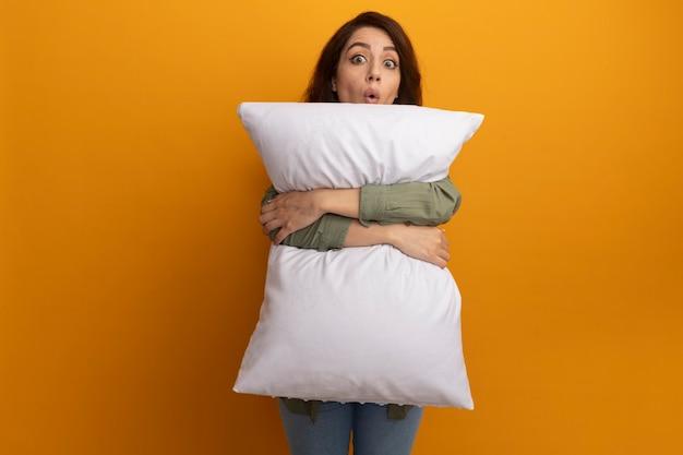 Удивленная молодая красивая девушка в оливково-зеленой футболке обняла подушку, изолированную на желтой стене с копией пространства
