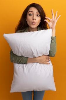 La giovane bella ragazza sorpresa che indossa la maglietta verde oliva ha abbracciato il cuscino che mostra la dimensione isolata sulla parete gialla