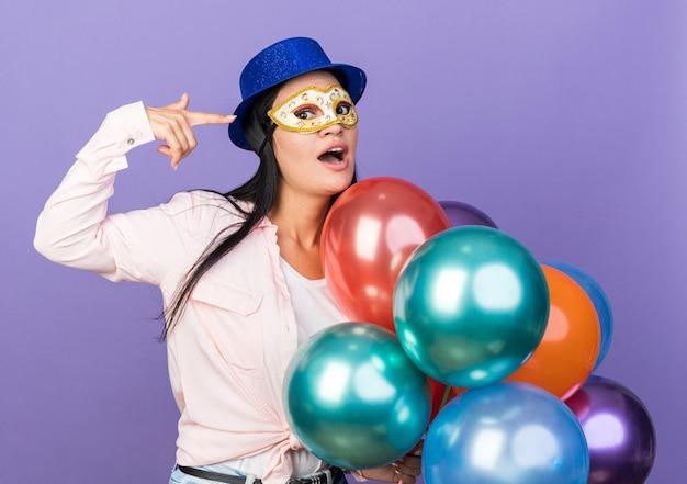 Удивленная молодая красивая девушка в шляпе для вечеринки и маскарадной маске для глаз, держащая воздушные шары, указывает на себя, изолированную на синей стене