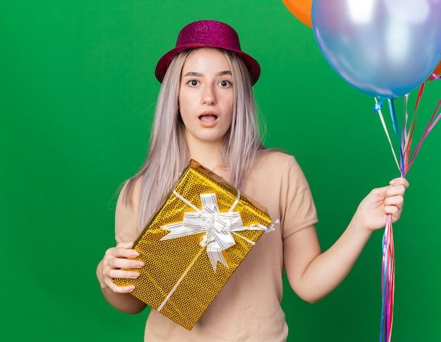 Sorpresa giovane bella ragazza che indossa cappello da festa e bretelle che tengono palloncini che tengono una scatola regalo