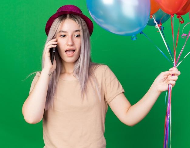 La giovane bella ragazza sorpresa che indossa il cappello da festa e le parentesi graffe che tengono i palloncini parla al telefono