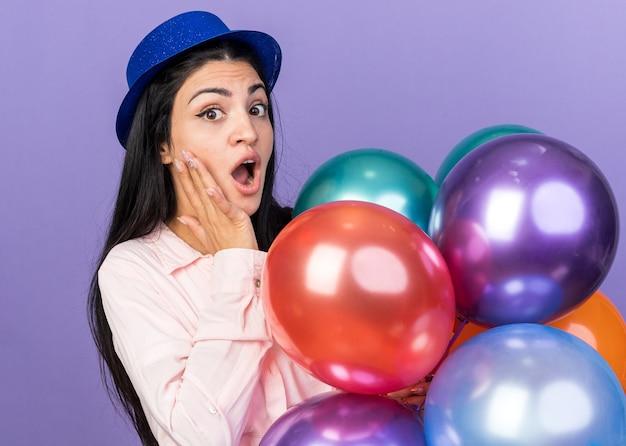 Giovane bella ragazza sorpresa che indossa il cappello del partito che tiene i palloni che mettono la mano sulla guancia isolata sulla parete blu