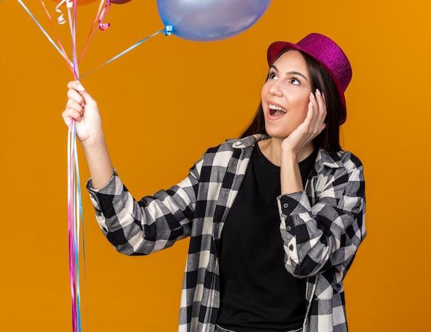 Удивленная молодая красивая девушка в шляпе, держащая воздушные шары, положив руку на щеку, изолированную на оранжевой стене