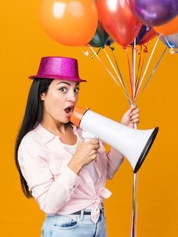 풍선을 들고 파티 모자를 쓰고 놀란 젊은 아름다운 소녀는 주황색 벽에 고립 된 확성기에 말한다