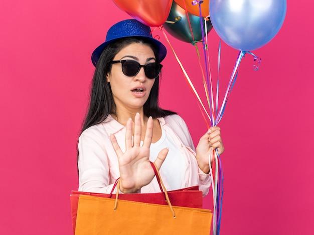 Удивленная молодая красивая девушка в партийной шляпе держит воздушные шары с подарочными пакетами, показывая жест остановки, изолированный на розовой стене