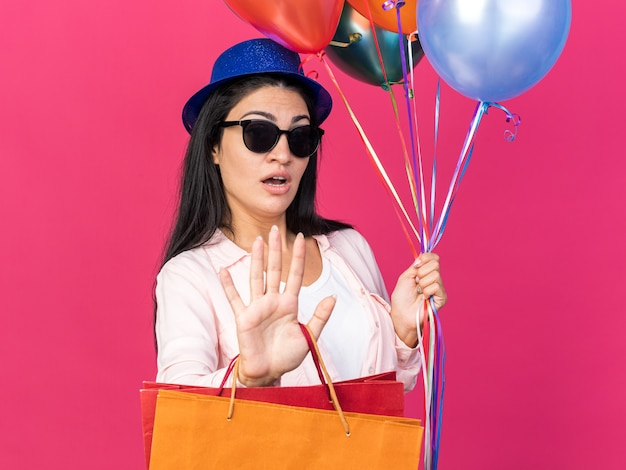 Sorpresa giovane bella ragazza che indossa un cappello da festa che tiene palloncini con sacchetti regalo che mostrano il gesto di arresto isolato sulla parete rosa