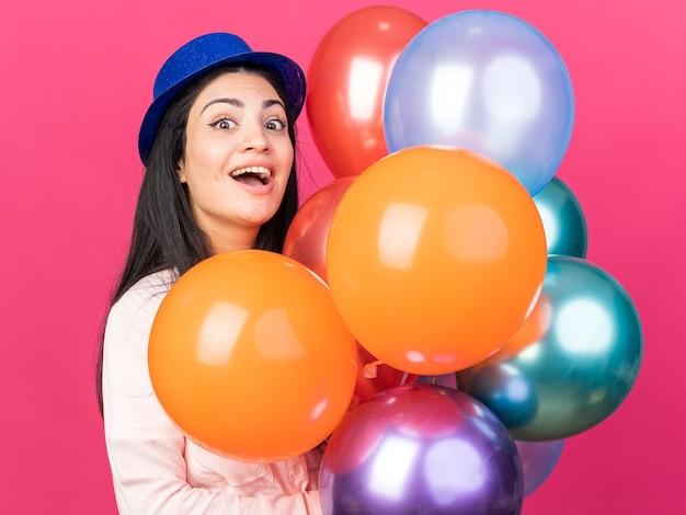 風船を持ってパーティーハットをかぶって驚いた若い美しい少女