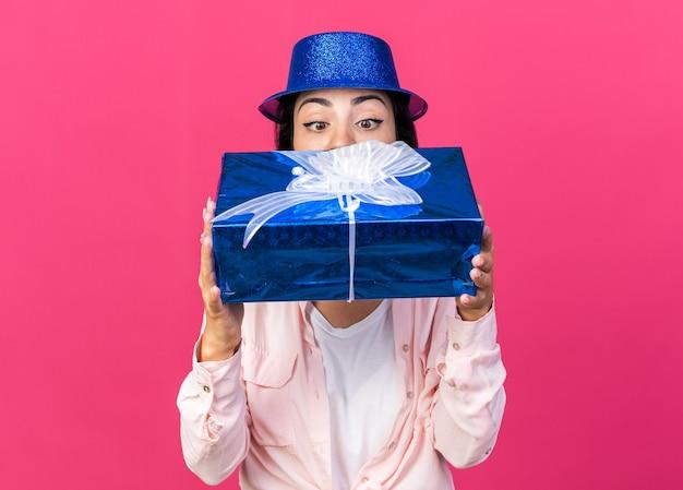 Giovane bella ragazza sorpresa che indossa un cappello da festa che tiene in mano e guarda la confezione regalo