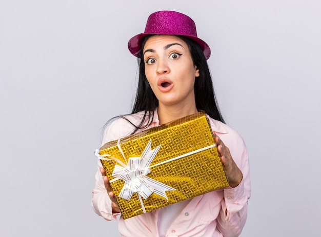 Surprised young beautiful girl wearing party hat holding out gift box at camera