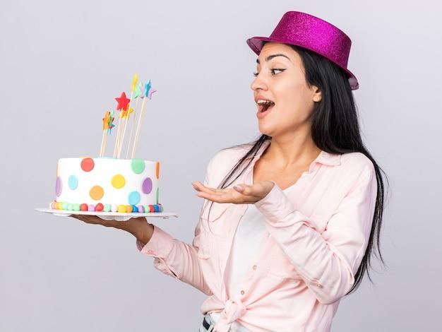 Sorpresa giovane bella ragazza che indossa cappello da festa che tiene e indica la torta isolata sul muro bianco