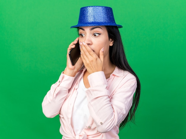 Surprised young beautiful girl wearing party hat speaks on phone covered mouth with hand