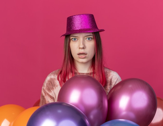Surprised young beautiful girl wearing party hat standing behind balloons isolated on pink wall