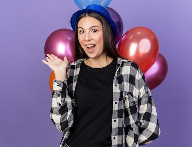Sorpresa giovane bella ragazza che indossa un cappello da festa in piedi davanti a palloncini