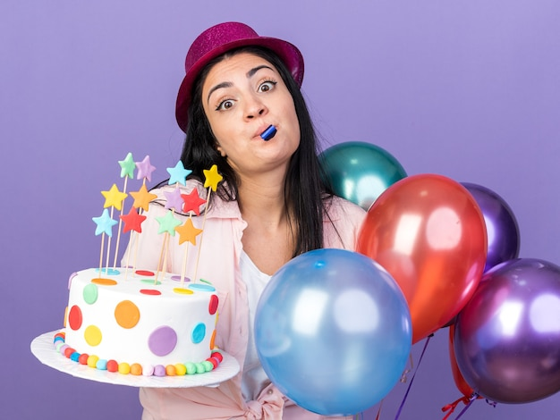 Surprised young beautiful girl wearing party hat standing nearby balloons holding cake blowing party whistle