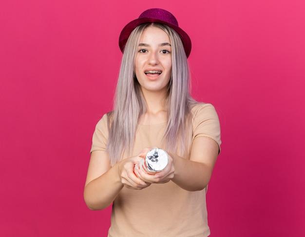 Sorpresa giovane bella ragazza che indossa un cappello da festa con bretelle dentali che regge un cannone di coriandoli alla telecamera
