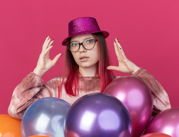 Surprised young beautiful girl wearing party hat with glasses standing behind balloons
