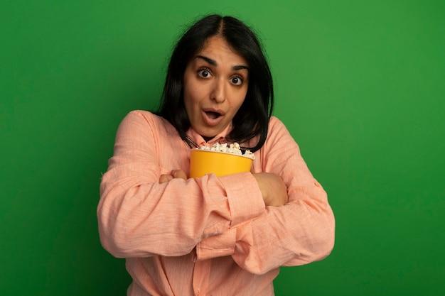 분홍색 티셔츠를 입고 놀란 젊은 아름 다운 소녀 녹색 벽에 고립 된 팝콘 양동이 포옹