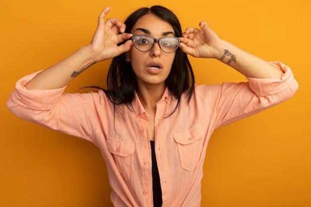 Giovane bella ragazza sorpresa che indossa la maglietta rosa che indossa e che tiene i vetri isolati sulla parete gialla