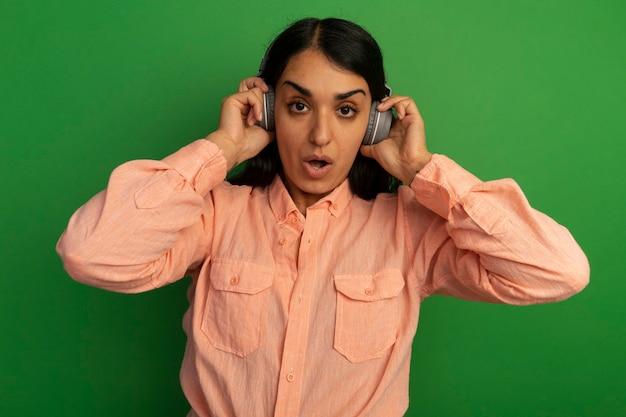 Удивленная молодая красивая девушка в розовой футболке с наушниками изолирована на зеленой стене