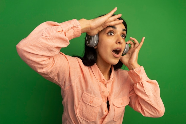 Удивленная молодая красивая девушка в розовой футболке с наушниками смотрит вдаль с рукой, изолированной на зеленой стене