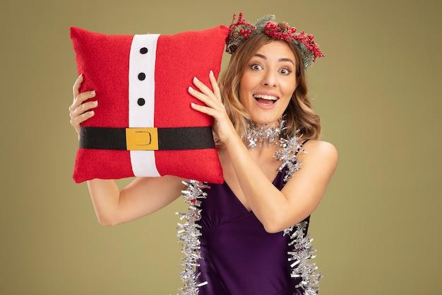 紫色のドレスと花輪を身に着けている驚きの若い美しい少女は、オリーブグリーンの背景で隔離のクリスマス枕を保持している首に花輪