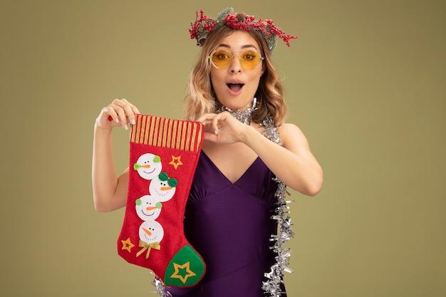 Удивленная молодая красивая девушка в фиолетовом платье и венке с очками и гирляндой на шее, держащая рождественский носок на оливково-зеленом фоне