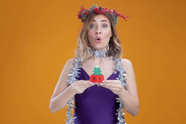 Giovane bella ragazza sorpresa che indossa vestito viola e corona con ghirlanda sul collo che tiene giocattolo di natale isolato su sfondo marrone brown