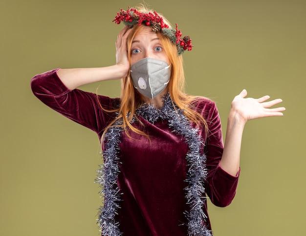 花輪と医療マスクと花輪と医療マスクを身に着けている驚いた若い美しい少女は、オリーブグリーンの背景で隔離の手を広げて頭に手を置いて花輪を首に