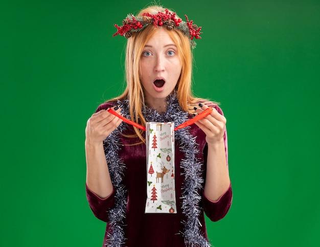 Sorpresa giovane bella ragazza che indossa un abito rosso con ghirlanda e ghirlanda sul collo tenendo la borsa regalo isolata sul muro verde green