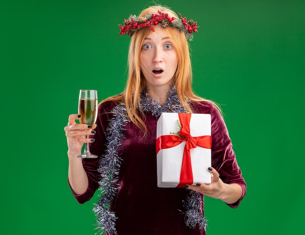 Giovane bella ragazza sorpresa che porta vestito rosso con la corona e la ghirlanda sul collo che tiene un bicchiere di champagne con confezione regalo isolato su priorità bassa verde