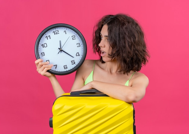 Surprised young beautiful traveler woman holding suitcase and clock and looking at clock on isolated pink wall