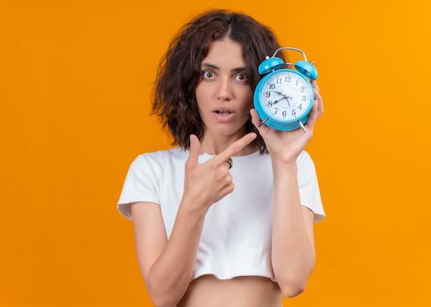 Giovane bella donna sorpresa che tiene sveglia e che indica esso sulla parete arancione isolata con lo spazio della copia