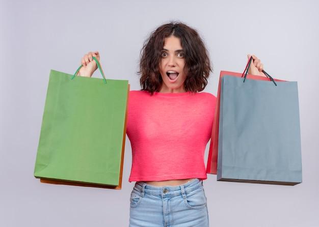 Giovane bella donna sorpresa che tiene i sacchetti di cartone sulla parete bianca isolata